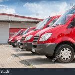 stock-photo-row-of-red-delivery-and-service-van-trucks-and-cars-in-front-of-a-factory-and-warehouse-140843719